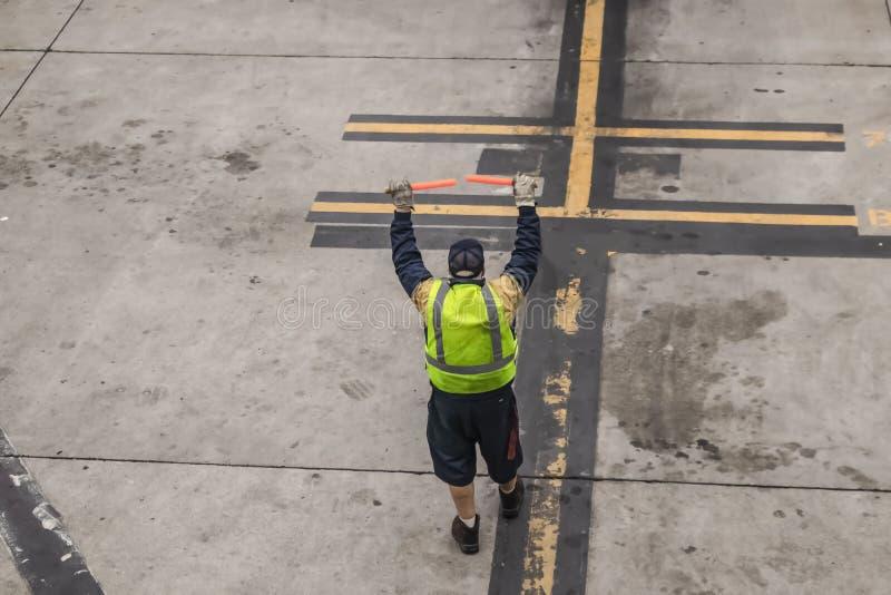 Unrecognizable lotniskowy pracownik dostaje gotowym prowadzić airplne wewnątrz lądować z czerwonymi migaczy kijami obraz royalty free