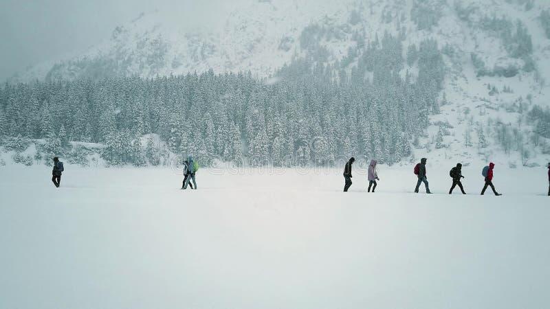 Unrecognizable ludzie wycieczkuje na śnieżnym jeziorze zdjęcia royalty free