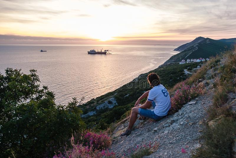 Unrecognizable mężczyzna siedzą na wzgórzu i podziwiają zmierzch na górze z seascape widoku plecy widokiem zdjęcie stock