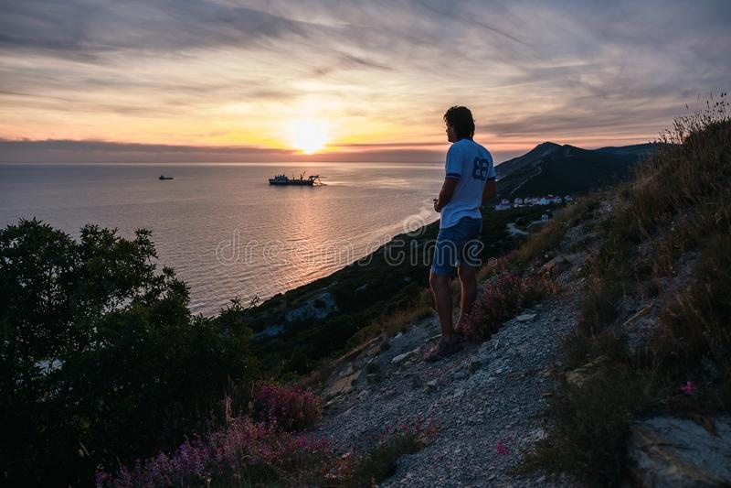 Unrecognizable mężczyzna stojaki na wzgórzu i podziwiają zmierzch na górze z seascape widoku plecy widokiem zdjęcia royalty free