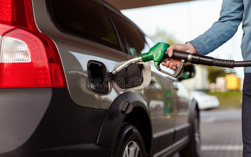 Crop man refueling car on filling station stock photos