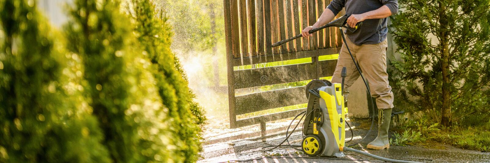 Unrecognizable man cleaning a wooden gate with a power washer. High pressure water cleaner used to DIY repair garden gate. royalty free stock photos