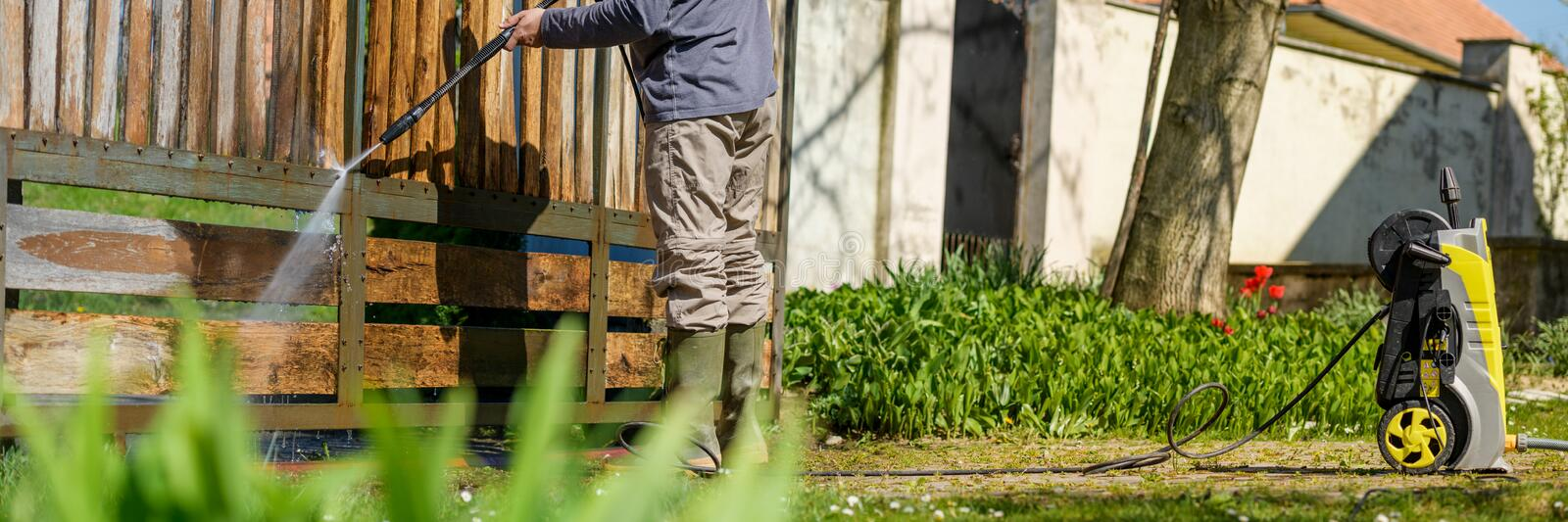 Unrecognizable man cleaning a wooden gate with a power washer. High pressure water cleaner used to DIY repair garden gate. royalty free stock photography