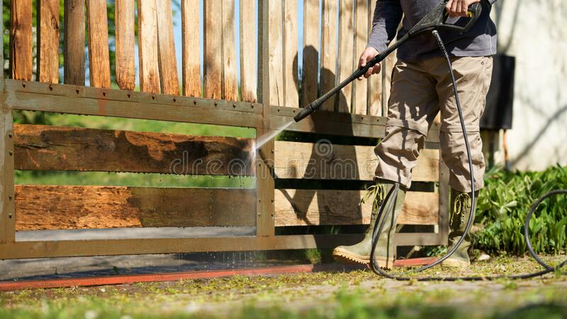 Unrecognizable man cleaning a wooden gate with a power washer. High water pressure cleaner used to DIY repair garden gate. royalty free stock photography