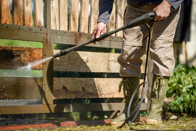 Unrecognizable man cleaning a wooden gate with a power washer. High water pressure cleaner used to DIY repair garden gate. stock photo
