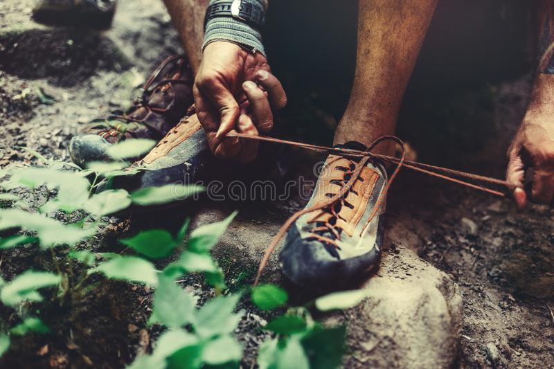 Man Dresses Climbing Shoes For Climbing, close-up. Extreme Hobby Outdoor Activity Concept. Unrecognizable Man Climber Dresses Climbing Shoes And Ties Up The stock photos