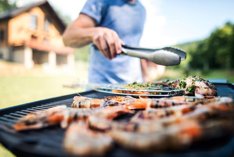 Unrecognizable man cooking seafood on a barbecue grill in the backyard. Unrecognizable man cooking seafood on a barbecue grill in the backyard on a sunny day stock photo