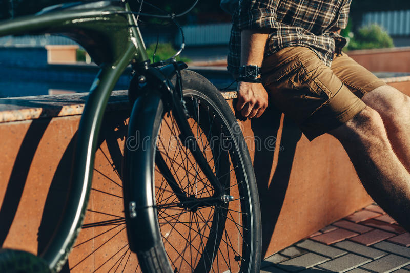 Unrecognizable Man Cyclist Sitting On Fountain Next To Bicycle In Summer Park Daily Lifestyle Urban Resting Concept. Young Man Cyclist Sitting With Sunglasses royalty free stock photo