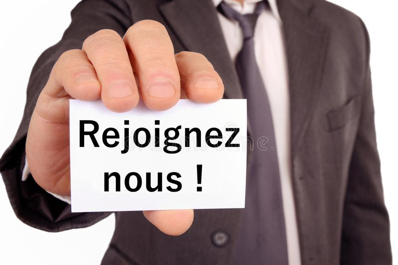 Join us written in French on a card. Unrecognizable man holding a card in hand on which is written in French join us stock photography