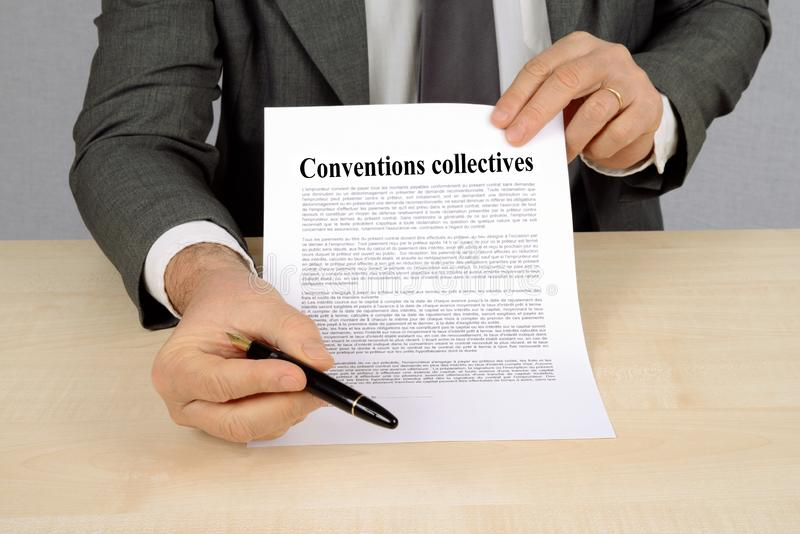 Collective agreements written in French. Unrecognizable man holding a document of collective agreements royalty free stock photo