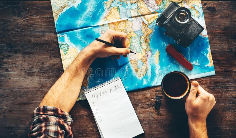 Unrecognizable Traveler Man Is Planning Vacation Travel With Map, Top View. He Drinks Coffee And Marks royalty free stock photos