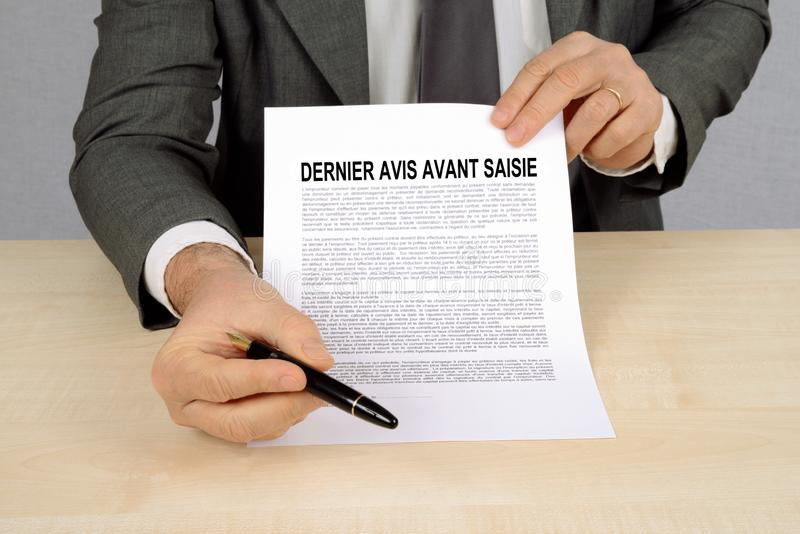 Last notice before seizure written in French. Unrecognizable man presenting a warning form stock photos
