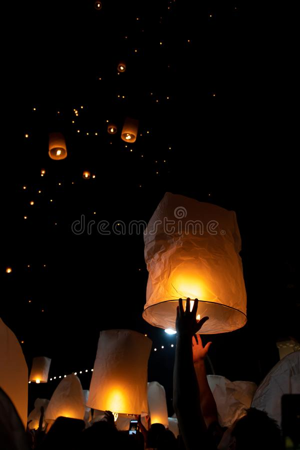 Unrecognizable man releasing paper lantern during Loi Krathong and Yi Peng festival in Chian Mai. With copy space stock photo