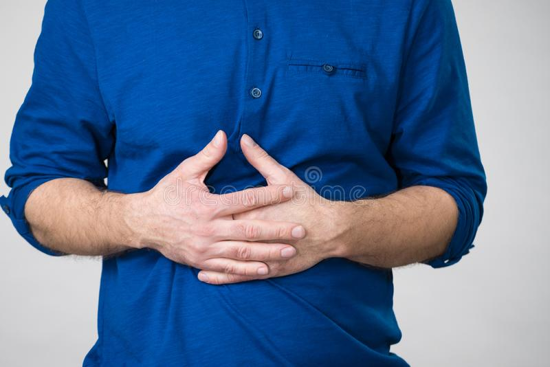 Man having crossed fingers on his stomach royalty free stock images