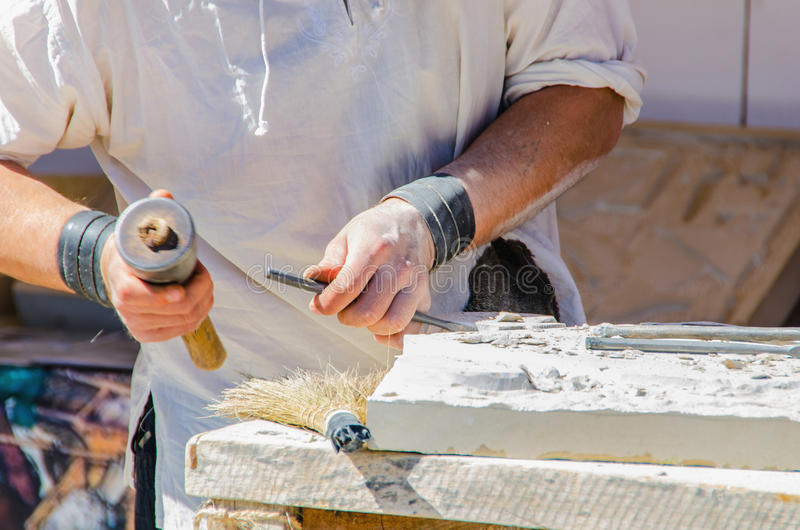 Unrecognizable man working with chisel on stone. Faceless man working with chisel. Sculpting on stone stock images