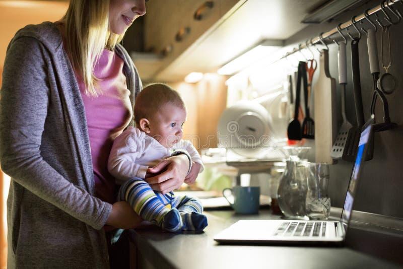 Unrecognizable matka z synem w rękach, laptop na kuchni co obraz royalty free