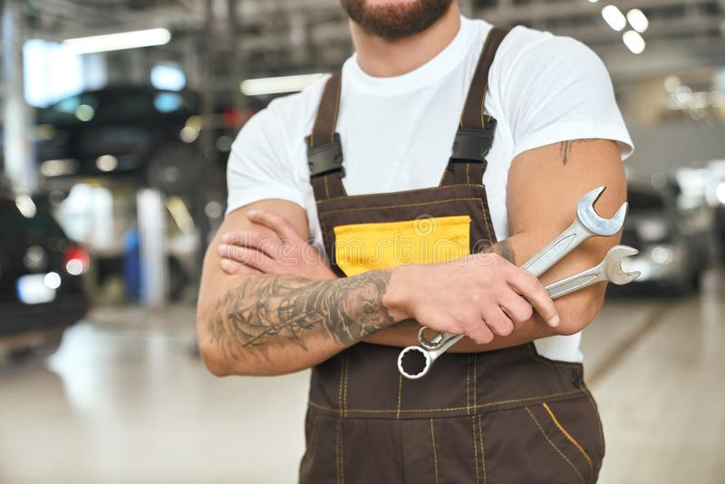 Unrecognizable mechanic in coveralls holding wrenches. Unrecognizable muscular mechanic with tattoed hands, wearing in coveralls and white t shirt. Brutal man stock photography