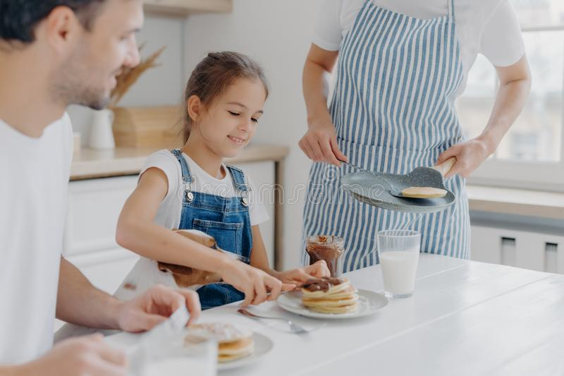 Unrecognizable mommy brings delicious pancakes to table, prepares breakfast for family. Cheerful girl adds melted chocolate to royalty free stock images