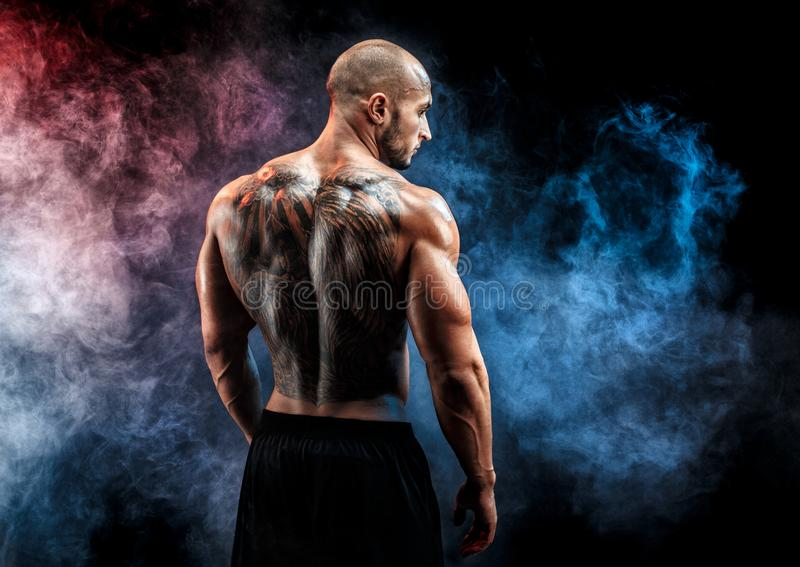 Unrecognizable muscular man with tattoo on back against of black background. Isolated. Unrecognizable muscular man with tattoo on back against of smoke stock images