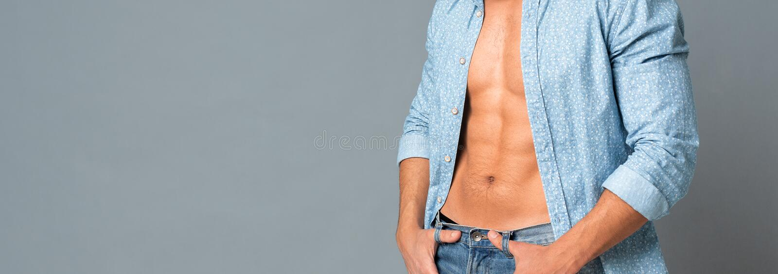 Unrecognizable Muscular Man In Unbuttoned Shirt Showing His Perfect Abs. Muscular Male Model In Unbuttoned Shirt Showing His Naked Torso And Perfect Abs royalty free stock image