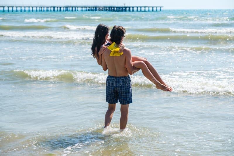 Unrecognizable para brunetki Mężczyzna niesie kobiety w jego rękach przy morzem obraz royalty free
