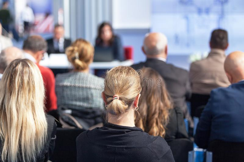 Presentation at a business or other professionals` conference. Unrecognizable participants at a business or other professionals` conference sitting, listening to stock images