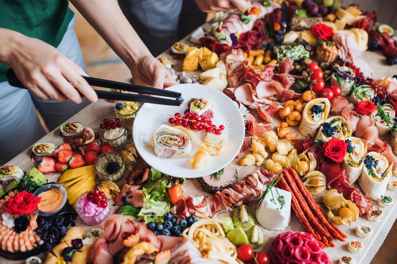 Unrecognizable people putting food on plates on a indoor family birthday party. royalty free stock photo