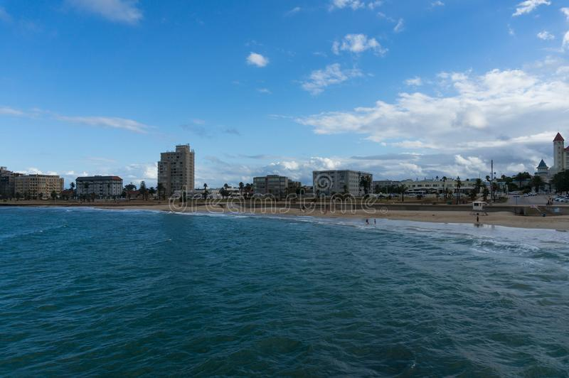 Unrecognizable people relaxing on the beach at Port Elizabeth, South Africa. Unrecognizable people relaxing on the beach with city view. Port Elizabeth, South royalty free stock photos