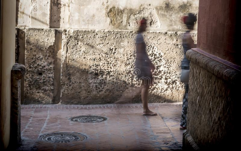 Unrecognizable people walk the typical narrow street of Seville, Andalusia, Spain. Concept of tourism stock photos