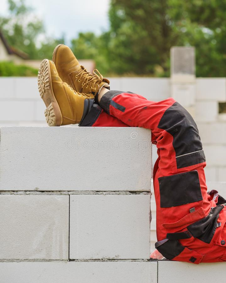 Person wearing red worker trousers. Unrecognizable person on construction site wearing protective worker red black pants trousers royalty free stock photography