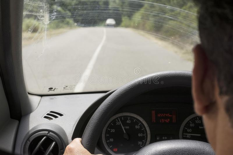 Unrecognizable person driving the car View of the road through the windshield royalty free stock photos