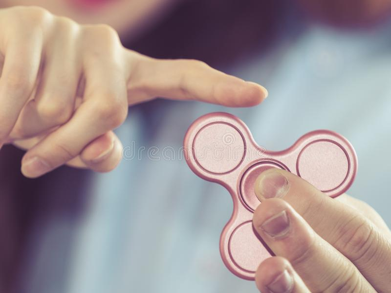 Person playing with fidget spinner stock image