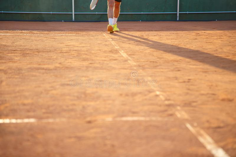 Person walking along the line of a ground tennis court stock images