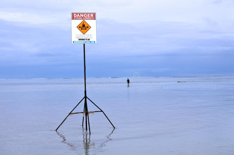 Danger Strong Currents - No Swimming sign Rarotonga Cook Islands. Unrecognizable person walks near a Danger Strong Currents - No Swimming sign. The most royalty free stock photos