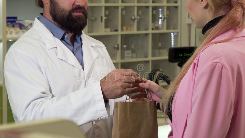 Unrecognizable pharmacist giving shopping bag with medicine to a customer. Cropped shot of a bearded male chemist selling medication to his female client royalty free stock photos
