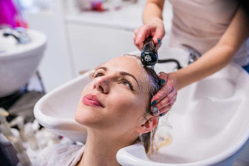 Unrecognizable professional hairdresser washing hair to her clie royalty free stock image