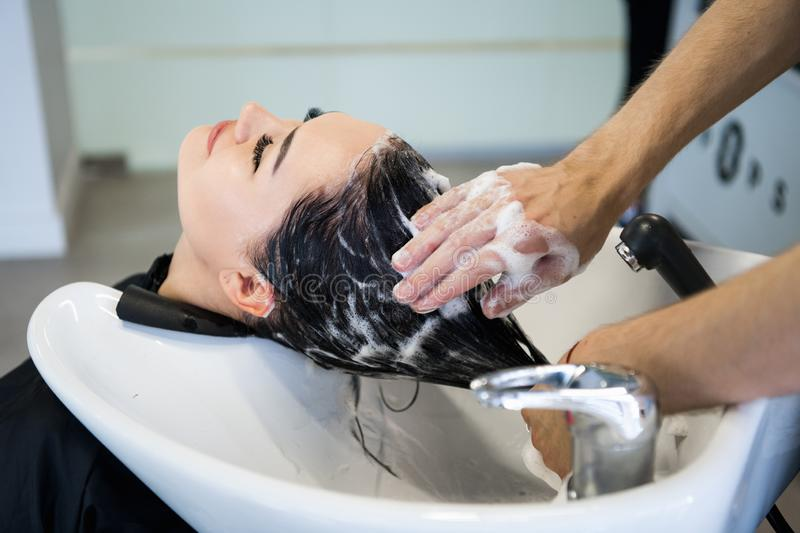 Unrecognizable professional hairdresser washing hair to her client. Beautiful hairdresser washing hair to her client royalty free stock image