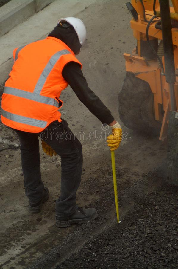 Road worker during asphalt work repair. Unrecognizable road worker during asphalt work repair in city road. Copy space stock image