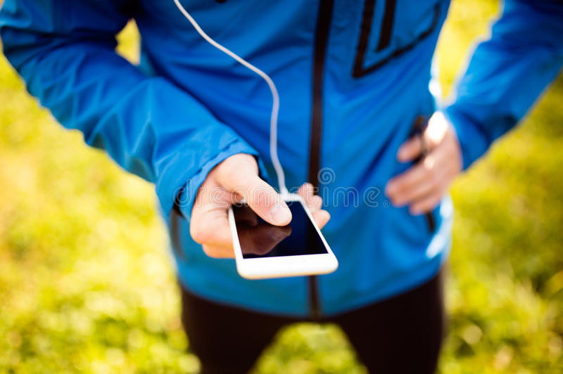 Unrecognizable runner with smart phone, using fitness app royalty free stock photo