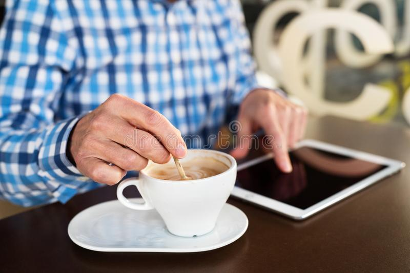 Unrecognizable senior businessman working on tablet in cafe. Sunny spring day royalty free stock photography