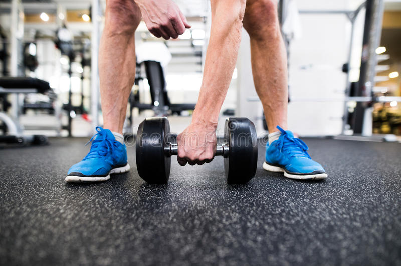 Unrecognizable senior man in gym working out with weights royalty free stock photography