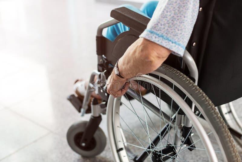 Senior person sitting in wheelchair. Unrecognizable senior person sitting in wheelchair royalty free stock photo