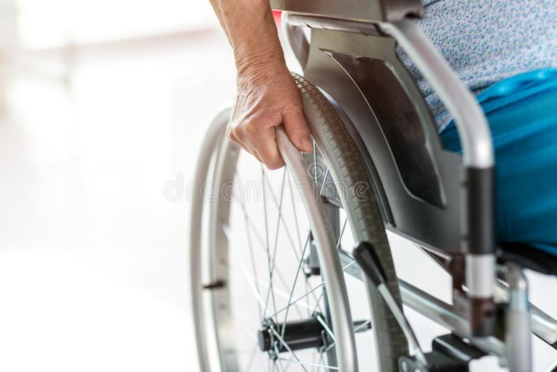 Senior person sitting in wheelchair. Unrecognizable senior person sitting in wheelchair stock photo