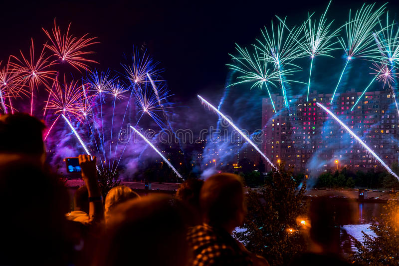 Unrecognizable Silhouettes of Crowd in city watch and shoot fireworks at night. New Year holiday celebration, display royalty free stock photos