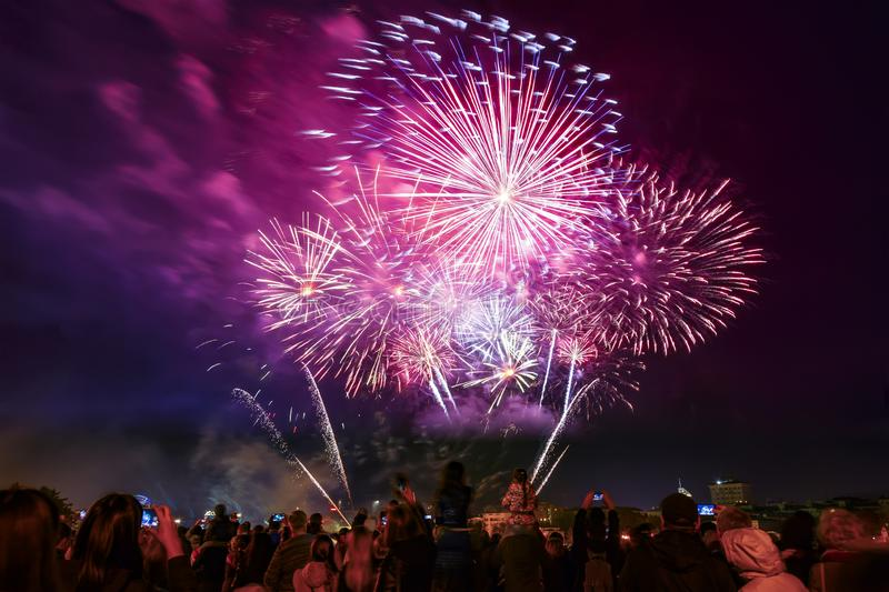 Unrecognizable Silhouettes of Crowd in city watch and shoot fireworks at night. New Year holiday celebration, festive royalty free stock image