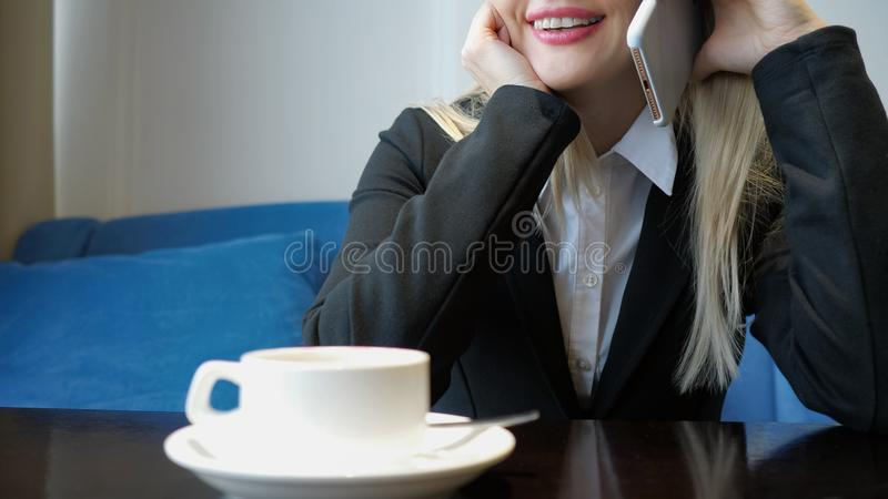 Unrecognizable smiling young woman having friendly phone conversation while drinking coffee in cafe. stock photography