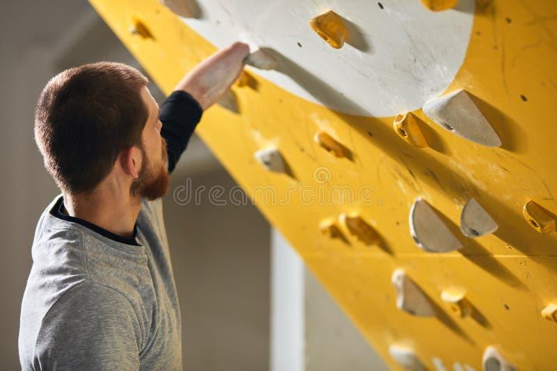 Unrecognizable sportowiec sprawdza chwyty przy pięcie ścianą bez przedramienia obraz stock