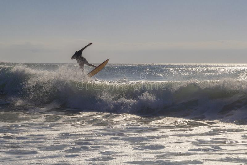 Unrecognizable surfer jumping over a wave, silhouetted against the sky at golden hour stock photography