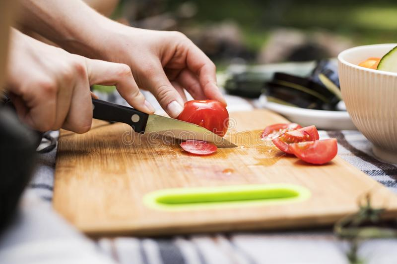 Unrecognizable teenagers camping and cooking. royalty free stock photography