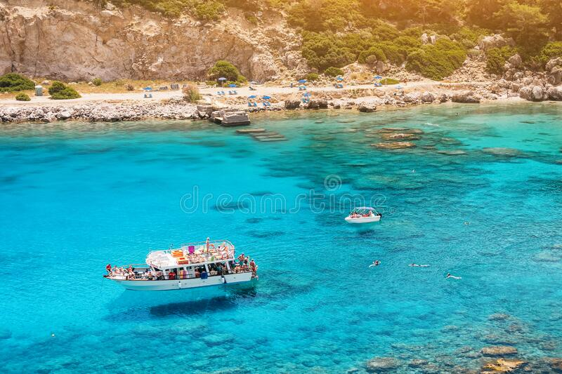 Tourists arrived on a cruise boat in the blue lagoon Bay and swimming in the sea. Concept of Paradise vacation and. Unrecognizable Tourists arrived on a cruise royalty free stock image